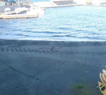Svastica disegnata sulla sabbia di Marina Piccola