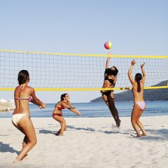 Four women playing volleyball on the sand beach.