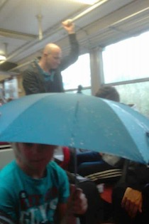 Turisti sui treni della Circum con gli ombrelli aperti