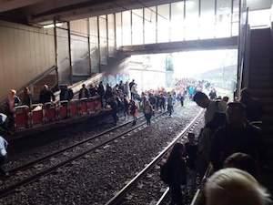 Treno Eav si ferma prima della stazione, passeggeri a piedi sui binari